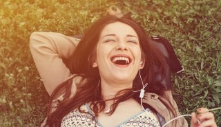 Woman with straight black hair, laying in the green grass with headphones in for Sunsilk's Conditioner page.