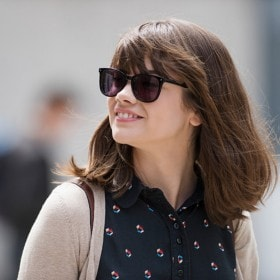 White woman with smooth hair, smiling and wearing sunglasses.